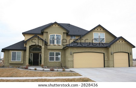 Green and gold new house with  three car garage