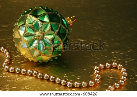 Green and gold ornament and gold beads on gold reflective, embossed paper.