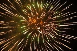 Green and golden color fireworks sparks with dark sky background