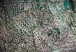 Green and grey camouflage net. Shallow depth of field.