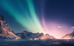 Green and purple aurora borealis over snowy mountains. Northern lights in Lofoten islands, Norway. Starry sky with polar lights. Night winter landscape with aurora, high rocks, beach. Travel. Scenery