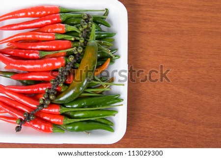 Green and red chili pepper on a wooden table