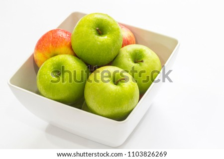 green and red fresh apples stack in white square bowl on white background