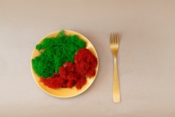 green and red moss on a golden plate in the shape of the Yin yang symbol and a golden fork. Vegetarian dish made of moss, concept. Banner with a place for the text