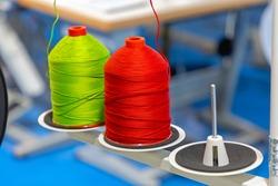 Green and Red Yarn Bobbin Spools at Sewing Machine