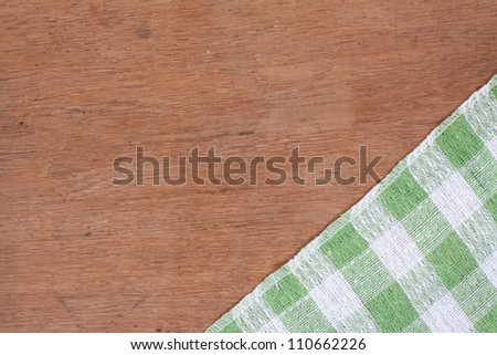 Green and white kitchen textile texture on wood background