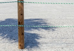 Green and white rope, attached to a wooden pole and in the shadow of a tree, are in place to keep vehicles and people out.