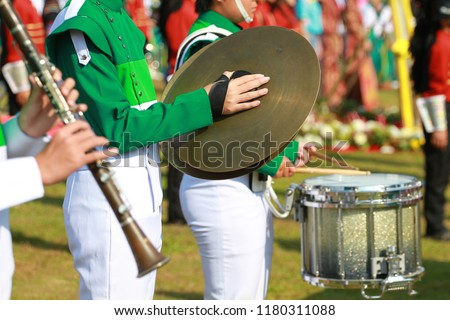 Green and white uniform cymbals player in marching band with drumer and clarinet player.