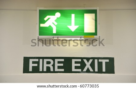 green and white warning sign glowing regarding fire exit emergency