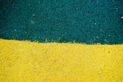 Green and yellow bright soft rubber flooring safe for sports and workout or on the playground from the many small round pebbles pressed. Background, texture.