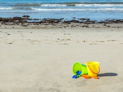 green and yellow child's sand pails with orange and blue  shovels in the sand at an ocean beach on a sunny summer day with copy space