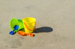 green and yellow child's sand pails with orange and blue shovels in the smooth sand at a beach on a sunny summer day with copy space