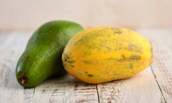 Green and yellow, colors of the Brazilian flag, present in avocado and papaya, on the wooden floor. Selective focus.