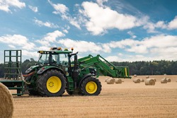 Green and yellow Tractor - modern farm equipment in field.