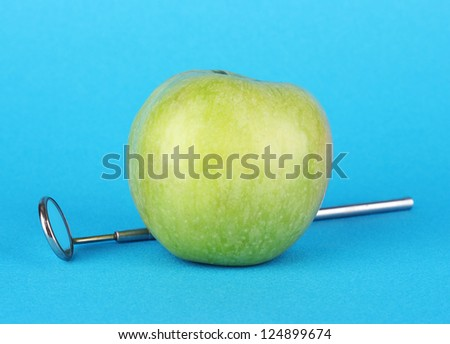 Green apple and dental tool on color background
