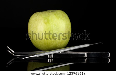 Green apple and dental tools isolated on black