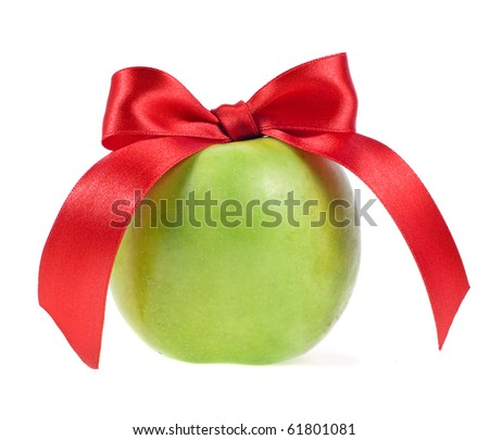 Green apple and red ribbon bow isolated over white background