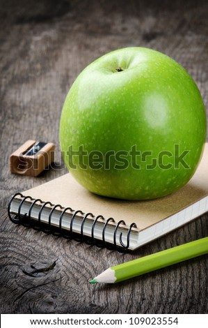 Green apple and school supplies. Ecological concept