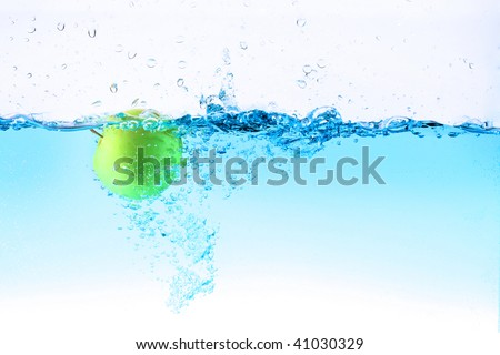Green apple are dropped into blue water