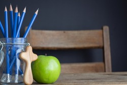 green apple, christian cross and jar of pencils on wood school desk with black background