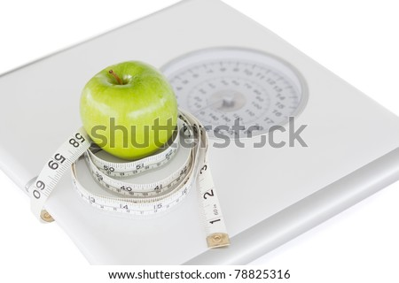 Green apple circled with a tape measure and weigh-scale against a white background