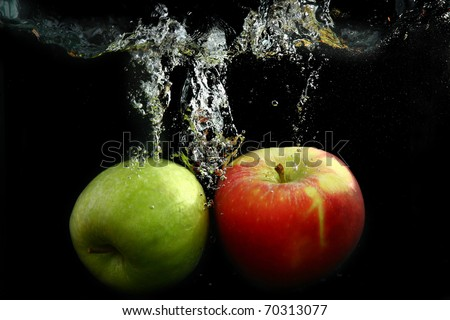 green apple dropped into water with splash isolated on black