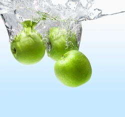 green apple dropping into water apple green juicy background.