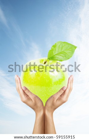 green apple in hands over sky