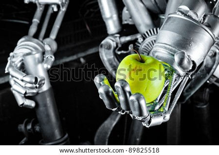 Green apple in the hands of a robot