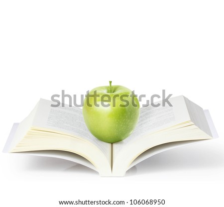 green apple on a book on a white background