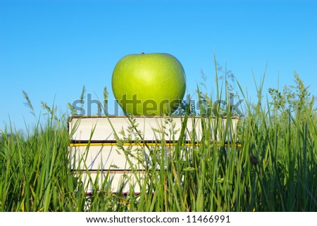 Green apple on stack of books in green grass