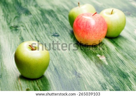 Green apple on the table, against the background of a red apple, side view