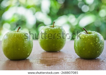 green apple on the table outside the home with natural light. according to the concept of freshness, health food and drinks or restaurants, supermarkets, green apple based products.