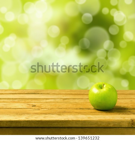 Green apple on wooden vintage table over bokeh background