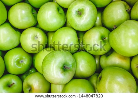 Green apple texture: lots of green apples. Apples storage. Bunch of green delicious apples in a box in supermarket