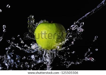 Green apple water splash on black background
