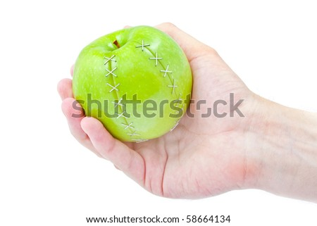 green apple with a scar in a masculine hand on white