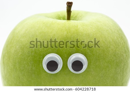 green apple with googly eyes on white background - portrait