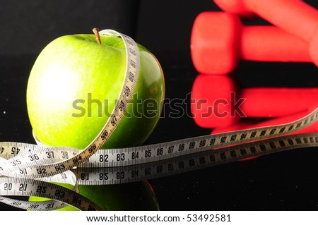 green apple with measure tape and red dumbbells