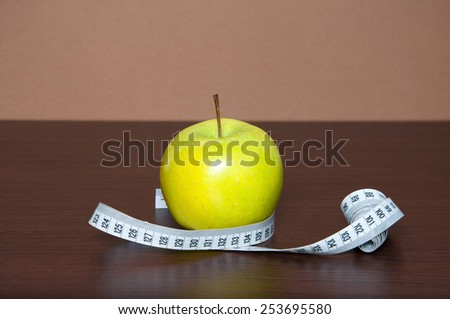 Green apple with measure tape on wooden table #253695580