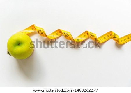 Green apple with measuring tape for the healthy diet slimming . Diet and Healthy Concept
