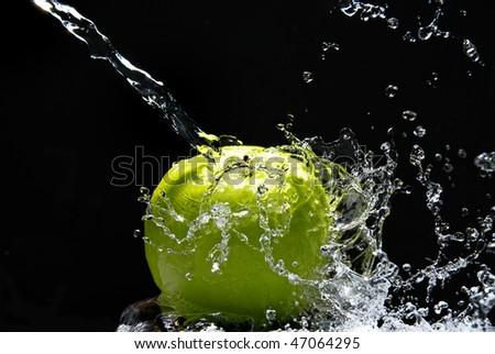 Green apple with water splash on black background