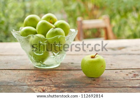 Green apples in a bowl on wood table.