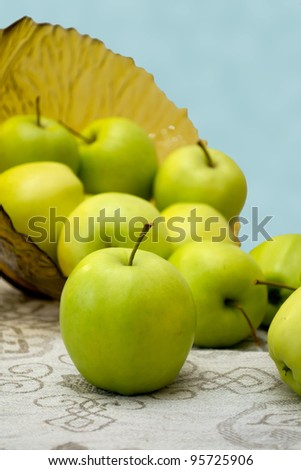 green apples in a glass vase on the table cloth