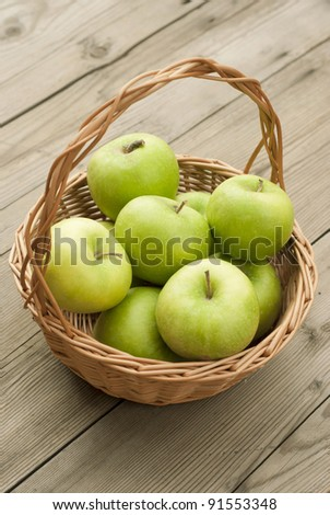 green apples in basket, wooden table