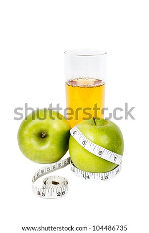 Green apples with measurement tape with glass of fresh apple juice on white background