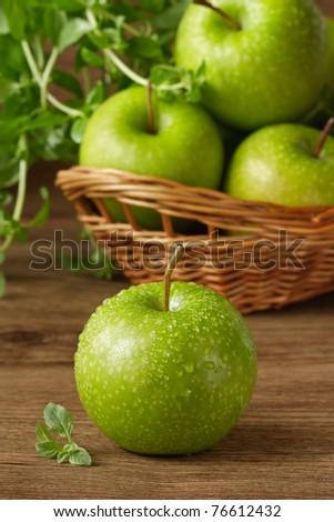 Green apples with water drops and fresh garden mint on a wooden table.
