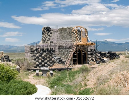 Green architecture - an earthship under construction in Taos County, NM. - stock photo