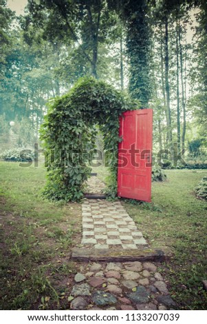 Green Archway in a garden with a red door