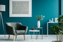 Green armchair against blue wall with silver painting in living room interior with plants